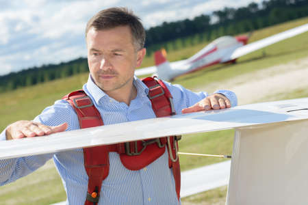 Man inspecting wing of glider