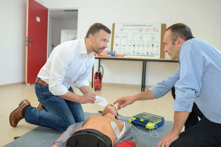 reanimate: Men doing first aid with dummy Stock Photo