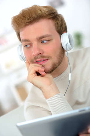 net surfing: Surfing the net whilst listening to music through his headphones Stock Photo