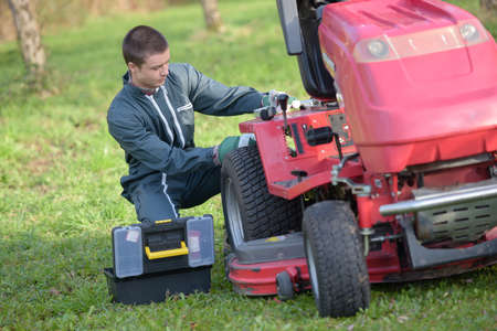 mow: Young man repairing ride on mower Stock Photo