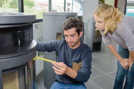 suitability: Man measuring woodburner on display