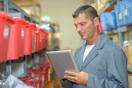 overalls: Warehouse worker using tablet