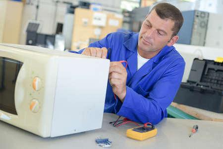 Techniker einen Mikrowellenherd zur Festsetzung Standard-Bild