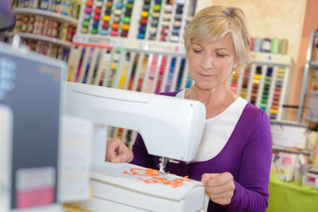 programmed: Lady using sewing machine in craft shop