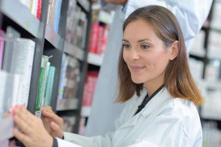 Female medic taking book from shelf
