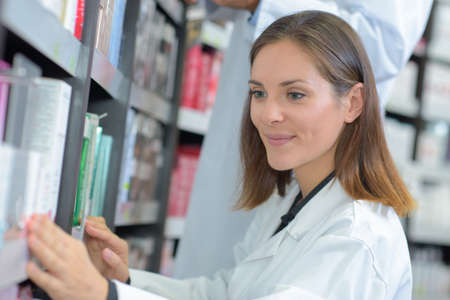 Female medic taking book from shelf Stok Fotoğraf - 65297206