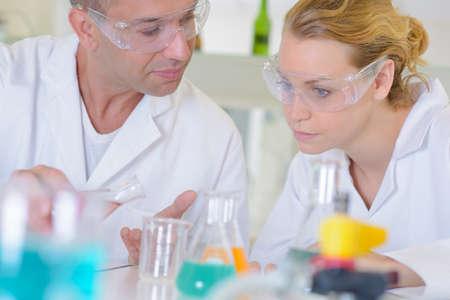 Male and female lab technicians conferring