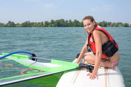 lifevest: girl doing windsurfing Stock Photo