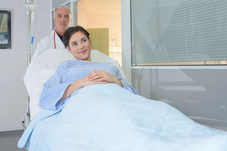 hospital patient: Doctor wheeling patient in hospital bed