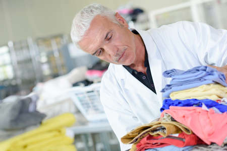 man laundry: Man in laundry with pile of washing