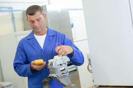 technical department: industrial technician reading a voltmeter
