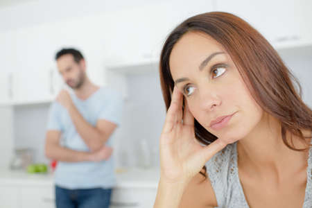 Woman looking fed up, partner in background