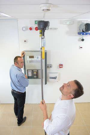 L'homme atteint pour tester le détecteur de fumée avec le poteau Banque d'images - 65299791