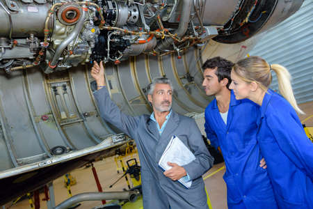 engineering teacher checking airplane engines with his students