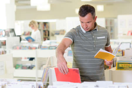 Man choosing book from trolley in library