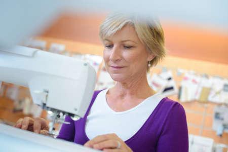 mature women: Senior woman using sewing machine
