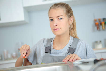 female plumber repairing a sink