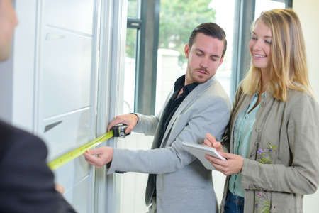 first time buyer: young couple measuring new house Stock Photo