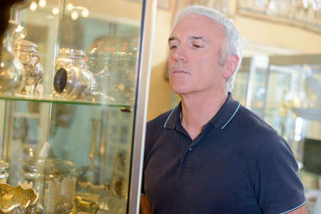Man looking into cabinet of antiques