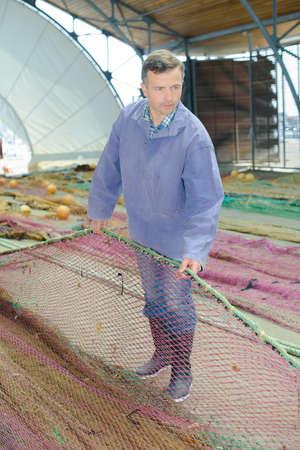 Fisherman untangling his nets