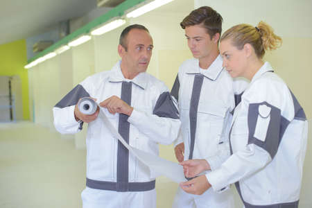 trainees: Decorator showing roll of paper to trainees Stock Photo