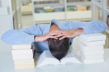 disheartened: Man resting head between two piles of books