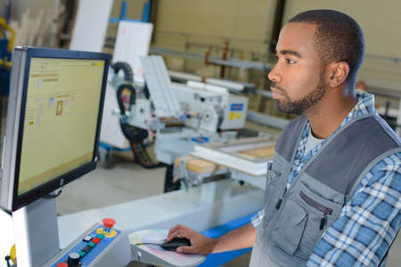 computerised: Man operating computer in industrial setting