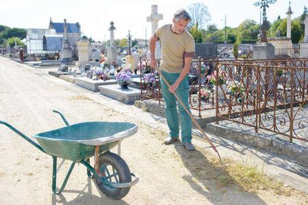 weeding: Man weeding around graves