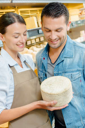 shop assistant: Shop assistant showing customer a whole cheese Stock Photo