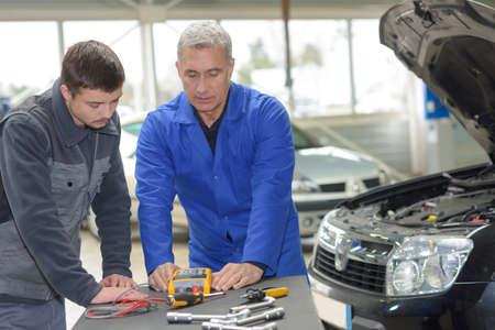 apprenticeships: student with instructor repairing a car during apprenticeship