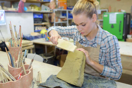 sculptor: Woman sculpting clay