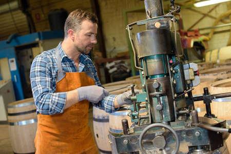cooper: Cooper using machinery Stock Photo