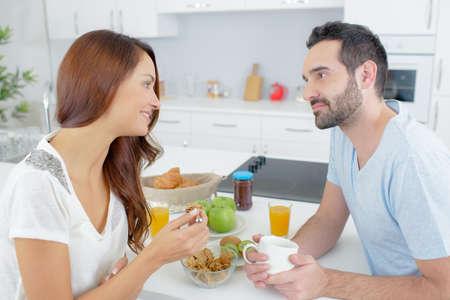 pareja en casa: par tener una conversación durante el desayuno