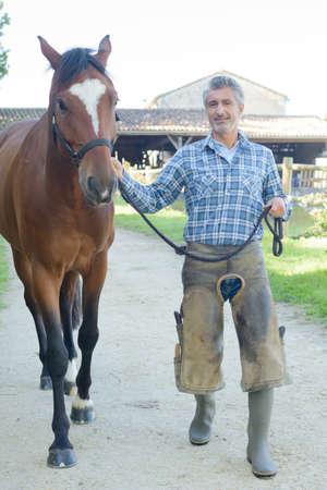 farrier: Farrier leading horse Stock Photo
