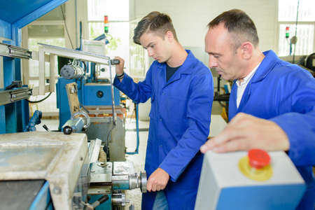 overseeing: Supervisor overseeing apprentice using machinery Stock Photo