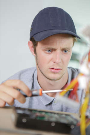 journeyman technician: Young electrician with puzzled expression Stock Photo