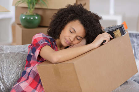 jaded: young woman sleeping on packing cases Stock Photo