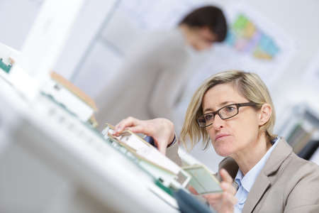 beautiful businesswoman with house model made from scale Stock Photo