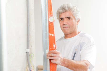 spirit level: Checking wall with a spirit level Stock Photo