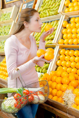 smelling: Young woman holding and smelling oranges from a stall Stock Photo