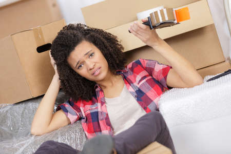 moving crate: exhausted woman with packages for house moving Stock Photo