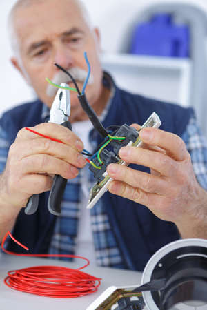 jumpsuite: senior electrician is fixing an outlet with pliers Stock Photo