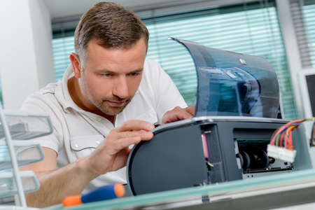 troubleshoot: Man repairing printer