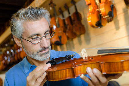luthier fixing a string Stock Photo