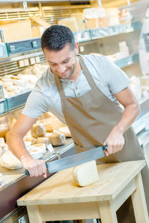 rich flavor: Local deli worker slicing some cheese