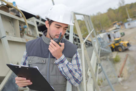 walkie talkie: Man in construction site with clipboard and walkie talkie Stock Photo