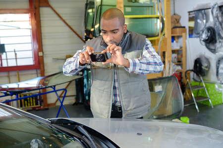 corroboration: Mechanic taking photograph of car Stock Photo