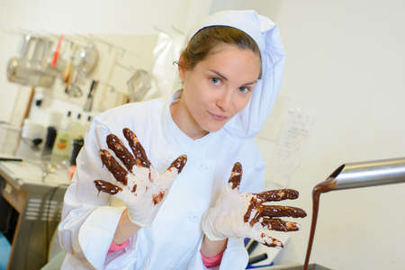 cake factory: chef with chocolate on fingers