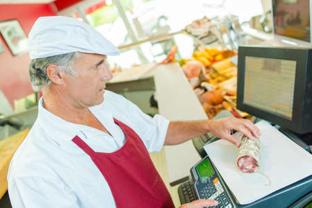 siervo: Butcher weighing some meat Foto de archivo