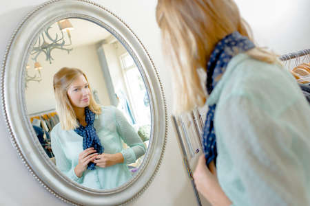 trying: Lady trying on scarf, looking at reflection in mirror Stock Photo